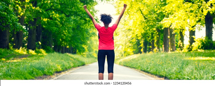 Panoramic web banner beautiful mixed race African American young woman girl teenager fitness running jogging celebrating success on road lined with spring or summer green trees