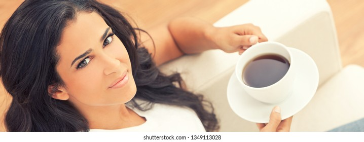 Panoramic web banner beautiful young Latina Hispanic woman or girl with a wonderful enigmatic smile drinking tea or coffee from a white cup at home on her sofa