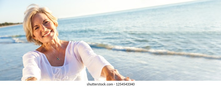 Panoramic web banner happy senior woman dancing and reaching with her hands on a deserted tropical beach