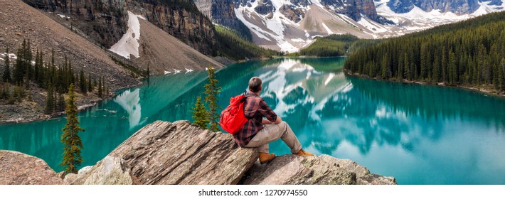 Panoramic web banner hiking man sitting down with rucksack backpack sitting on tree log by Moraine Lake looking at snow covered Rocky Mountain peaks, Banff National Park, Alberta Canada