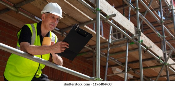Panoramic web banner image male builder foreman, construction worker or architect on site holding a clipboard and drinking a mug of coffee or tea
