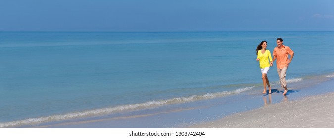 Panoramic web banner man and woman romantic couple running holding hands on a deserted tropical beach with bright clear blue sky