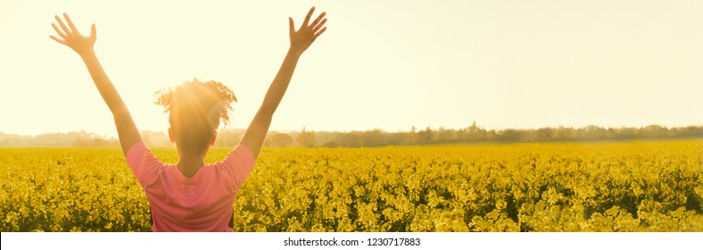 Panoramic web banner of mixed race African American girl female young woman athlete runner teenager in golden sunset or sunrise arms raised celebrating in field of yellow flowers