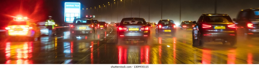 Panoramic web banner motion blurred photograph of traffic at in night in the rain on a British motorway with police officer and car
