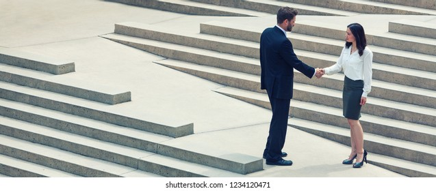 Panoramic web banner photograph of caucasian man businessman and an Asian woman businesswoman shaking hands on a deal standing on modern city steps