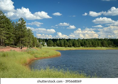 Panoramic, wide angle shot of tranquil Fool Hollow Lake, Arizona, USA with beautiful clouds in desert blue sky and lush green nature.