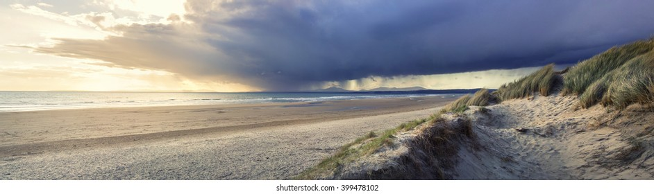 Panoramic wide-angle photograph showing a storm over the distant mountains of Snowdonia just before sunset on a spring evening. Sand dunes are visible in the foreground.
