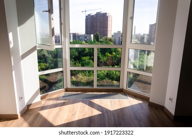 Panoramic window. Sharp shadows from the panoramic window frame on the wooden floor. Underfloor heater grill.