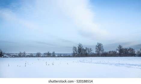 Panoramic winter landscape with snow field in countryside and trees on horizon