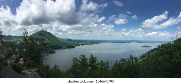 Panoramo view of the Hudson River Valley atop Breakneck Ridge trail in the midsummer with a mostly clear blue sky.