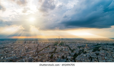 panormaic picture of paris areal view, the eiffel tower and dramatic clouds with sun rays in the evening