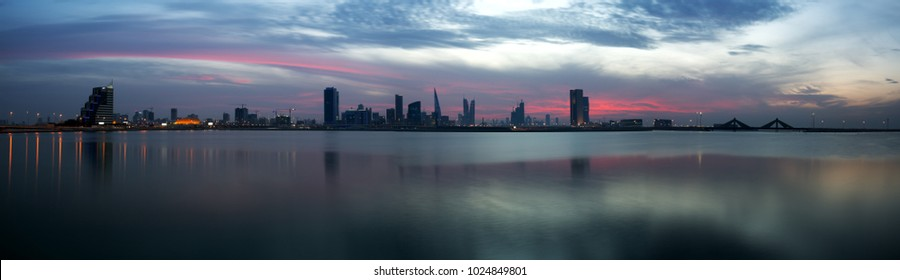 Panormic view of Bahrain skyline with dramatic clouds and reflection on water