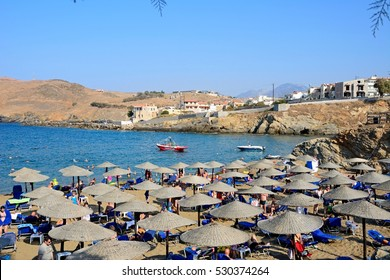 PANORMOS, CRETE - SEPTEMBER 15, 2016 - Tourists relaxing on the sandy beach with views towards the Aegean sea and rocky coastline, Panormos, Crete, Greece, Europe, September 15, 2016.