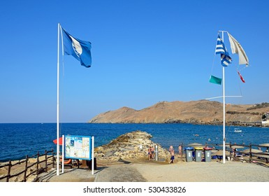 PANORMOS, CRETE - SEPTEMBER 15, 2016 - Flags and information boards on the edge of the beach with views towards the rocky coastline, Panormos, Crete, Greece, Europe, September 15, 2016.