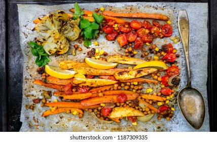 Pan-Roasted Chicken and Vegetables. Top view to easy food. Slice carrot, breast fillet, onion, sweet potato and cherry tomatoes. Add chickpeas, corn, some herbs, honey and olive oil. Bake in oven