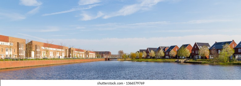 Panrorama with modern brick houses along water in a family friendly suburban neighborhood in Veenendaal in the Netherlands.