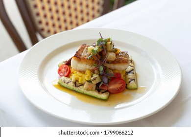 Pan-seared fish with risotto and summer vegetables - Shutterstock ID 1799066212