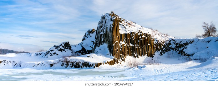 Panska skala - rock formation of pentagonal and hexagonal basalt columns. Looks like giant organ pipes. Covered by snow and ice in winter time. Kamenicky Senov, Czech Republic. - Shutterstock ID 1914974317