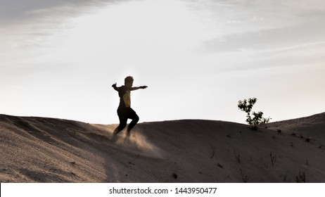 Pantai Klebang, Melaka - June 25, 2019:  A silhouette view of a man running and jumping happily at the sandy desert at Klebang Beach in Melaka