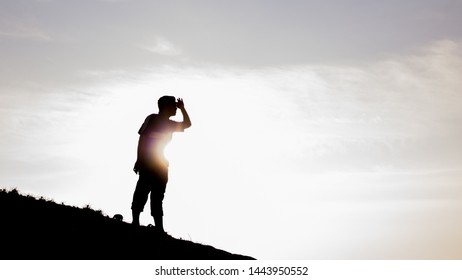 Pantai Klebang, Melaka - June 25, 2019: A silhouette view of a young man at the peak of sandy hill lost in the desert in Klebang Beach.