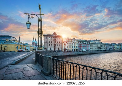 Panteleymonovsky bridge with a lantern across the Fontanka river in St. Petersburg and the embankment in the first rays of the dawn sun