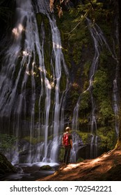 Panther Creek Falls with a hiker standing in awe.