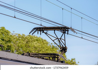 Pantograph of a train connecting on electric line, Electric railway train and power supply lines, Cables connections and metal pole overhead catenary wire.