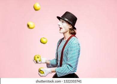 Pantomime with white facial makeup juggling with apples on the pink background in the studio