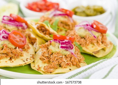 Panuchos - Mexican corn tortillas filled with refried beans and topped with shredded chicken, guacamole, pickled red onions and tomato. Tomato salsa and jalapenos side dishes.