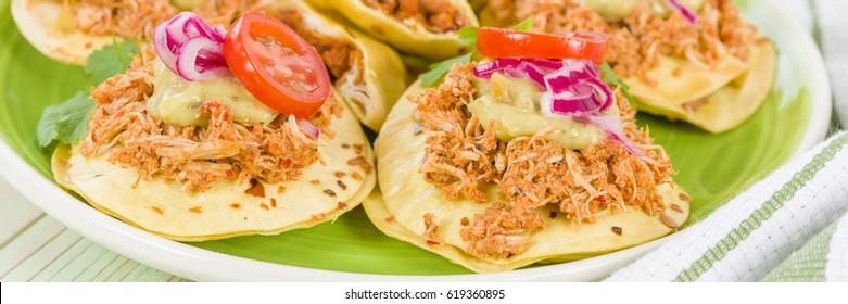 Panuchos - Mexican corn tortillas filled with refried beans and topped with shredded chicken, guacamole, pickled red onions and tomato.
