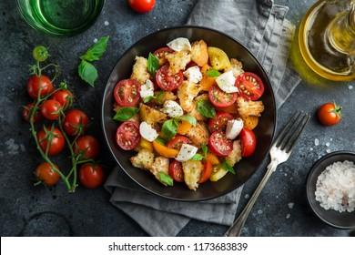 panzanella, traditional italian tomato, mozzarella and bread salad in black bowl, top view