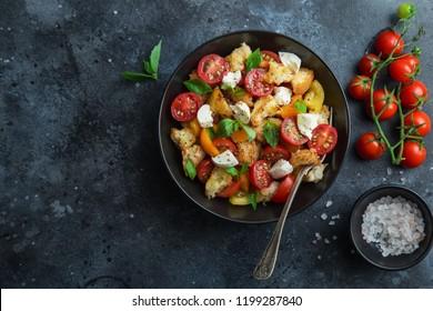 panzanella, traditional italian tomato, mozzarella and bread salad in black bowl, top view, copy space