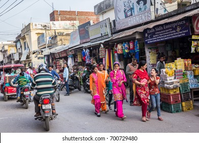 PAONTA SAHIB, INDIA - MARCH 22, 2017: men on motorbikes and women in colorful sarees in the market of Paonta Sahib, India, a Sikh pilgrimage destination.