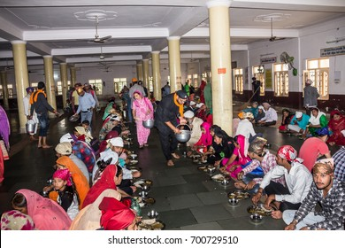 PAONTA SAHIB, INDIA - MARCH 22, 2017: Sikh believers are taking a common meal inside the Sikh temple of Paonta Sahib, india, a Sikh pilgrimage destination.