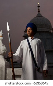 Paonta Sahib, India - May 22, 2009: A Sikh boy in white clothes, blue turban holding a spear outside at dusk at Paonta Sahib Gurudwara, famous for its past warriors