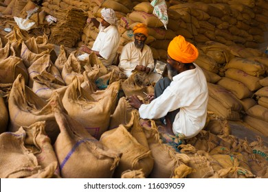Paonta Sahib, India - May 23, 2009: Sikh men packing burlap sacks full of charity grain in part of their philanthropic religious duties to help the needy