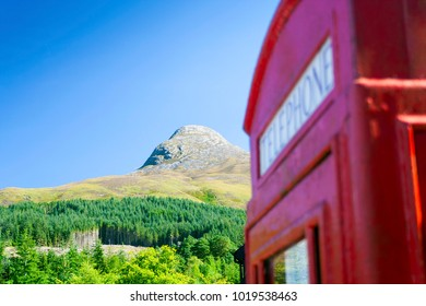 The Pap of Glencoe mountain in the Scottish Highlands named Sgurr na Ciche in Scottish Gaelic with a juxtaposition out of focus telephone box
