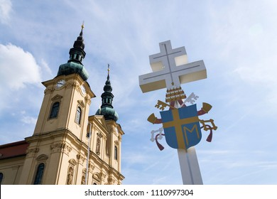 Papal coat of arms on cross in front of the Pilgrimage Basilica of the Assumption of the Virgin Mary and St. Cyril and Methodius at Velehrad Monastery, Moravia, Czech Republic