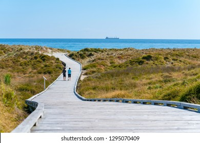 Papamoa winding walkway through sand dunes and outllok to horizon with two peopleTauranga New Zealand