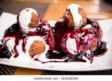 Papanasi - a traditional Romanian dessert. The cake is made from three donuts covered in sour cream and fruits jam