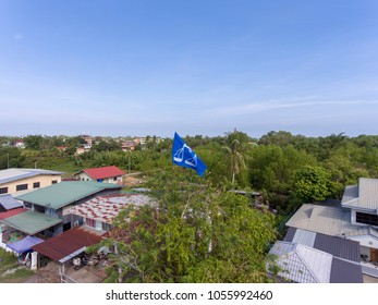 PAPAR, SABAH, MY - MAR 28, 2018: Barisan Nasional political campaign flag hoisted up high above tree lines for the Malaysian 14th general election in Mid 2018.