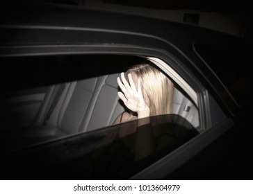 Paparazzi concept - invasion of privacy - young starlet blonde woman blocking her face while being photographed in a black limousine