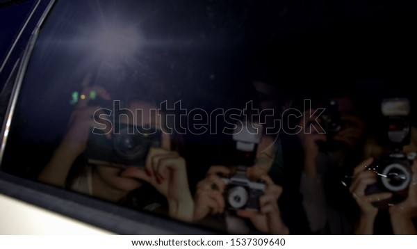 Paparazzi shooting tinned windows in luxury car, celebrity hiding inside, fame