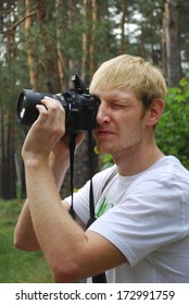 Paparazzi. Unshaven man with a camera in the summer forest.