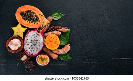 Papaya, Dragon Fruit, Cactus Fruit. Fresh Tropical Fruits. On a wooden background. Top view. Copy space.