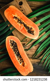 Papaya exotic fruit from Asia. One half of tropical fruit with knife and spoon on table. Black seeds in orange pulp