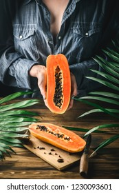 Papaya exotic fruit from Asia. One half of tropical fruit in Women hand. Black seeds in orange pulp