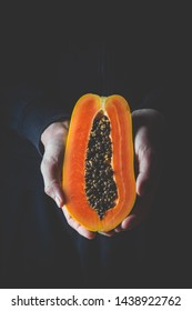 Papaya exotic fruit from Asia. One half of tropical fruit in a man's hand on dark background.