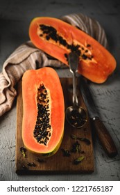 Papaya exotic fruit from Asia. Two halfs of tropical fruit on table. Black seeds in orange pulp