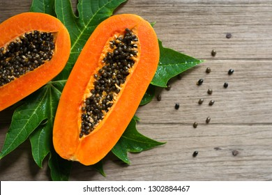 Papaya fruit on wooden background.Slices of sweet papaya on wooden background,Halved papayas